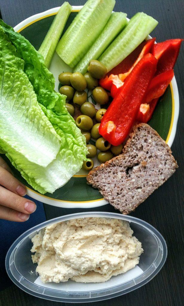 kromka chleba gryczanego, hummus, kilka liści sałatki rzymskiej, pół papryki czerwonej, pół ogórka świeżego